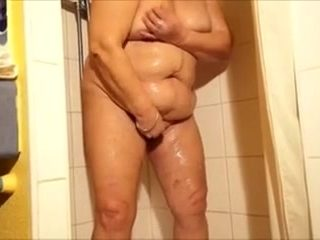 Granny in the shower rubs her moist love tunnel and fingers it