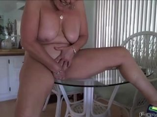 Big titted cougar masturbates on the table